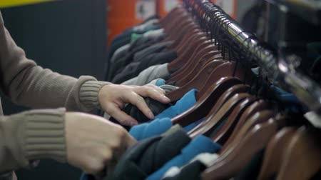 носить : Men sweaters and shirts in different colors on hangers in a retail clothes store, man choose hoodies close up in shop