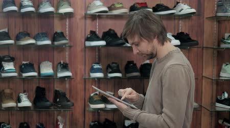 üzleti öltöny : Businessman Running Online Shoe Business With Digital Tablet, standing in sneaker extreme shop
