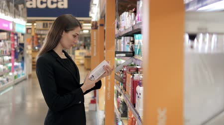 взятие : Beautiful Woman Choosing Body Care Products In Supermarket, Brunette in shopping center Стоковые видеозаписи