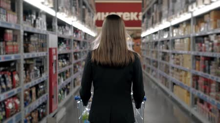 kordé : Woman shopping at the supermarket, follow shot from back of young woman with trolley in shopping center, alcohol store.