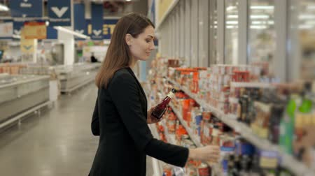 raflar : Portrait of positive woman girl buying conserve tomato sauce or balsamic vinegar in grocery shop Stok Video