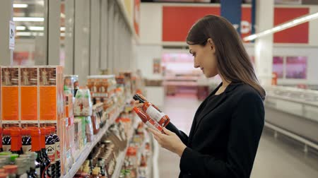 raflar : Portrait of positive woman girl buying conserve hot chilli tomato sauce or balsamic vinegar in grocery shop