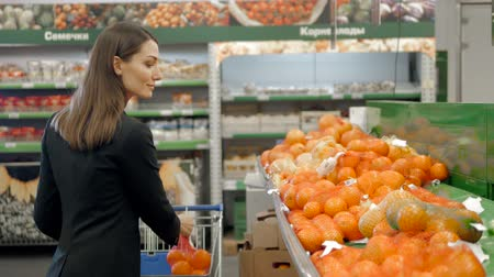 супермаркет : Beautiful women shopping vegetables and fruits in supermarket, brunette choose tomato and pepper, fresh salad