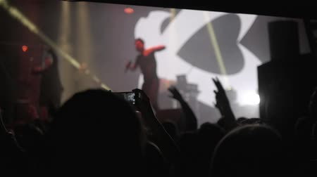 trussing : Silhouette of people holding their hands up at a concert. Blured musicians