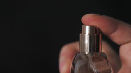 perfume bottle : close up of handsome young business man using perfume or deodorant on black background macro