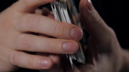 trik : Closeup of hands shuffling playing cards, dealer mix poker cards in casino close up macro