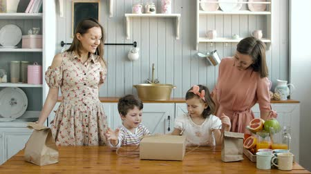 kisbaba : happy twins moms and his little daughter girl and boy child opening box on kitchen