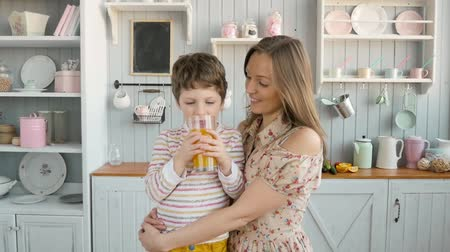 culinária : funny three years old child and woman mother with beige apron, in teamwork, drink juice and eat fruits at kitchen home, laughing happy together Stock Footage
