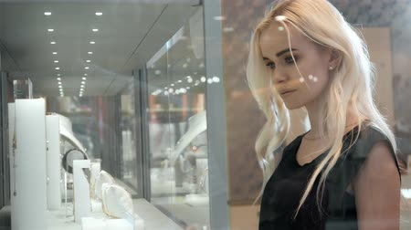 biżuteria : Young woman looking at the shop showcase and jewelry to look at it closer, beautiful student blonde fashion model in juwellery mall shopping