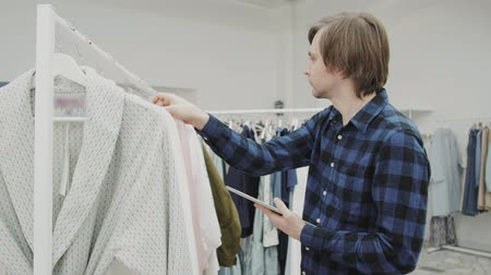 clothing : Half length portrait of happy male entrepreneur using digital tablet for job in her modern store with womans clothes, smiling consultant holding touch pad while standing in brandy shop Stock Footage