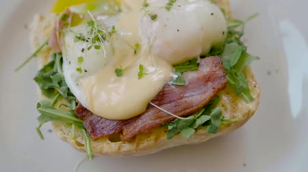 poached egg : Eggs Benedict with bread and tomato on a plate with becon morning sandwich