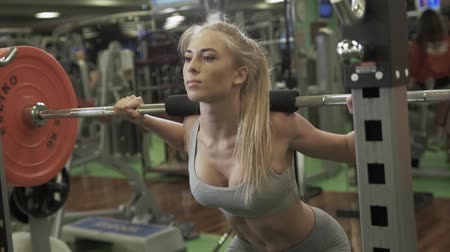 eşek : Young sexy blonde european girl in the gym doing squat with barbell in front of the mirror. She is dressed in sports clothes (white top, gray leggings, sneakers)