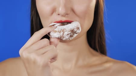 bécsi kifli : happy girl holds a doughnut and bites one of them, slow motion woman eat donut, sexy shot on chroma green blue key screen