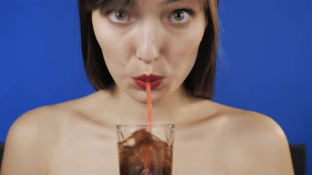szomjúság : Woman drinking a glass of cola with ice. Make bubbles blow into the tube