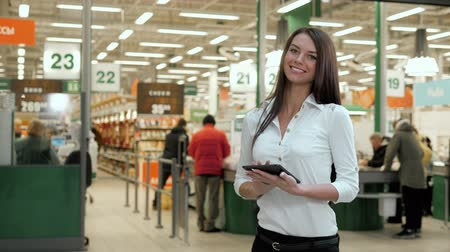 foco no primeiro plano : Woman with digital tablet in shopping centre and looking at camera and smiling grocery shop