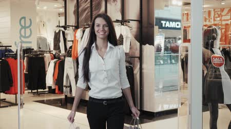 péntek : happiness, consumerism, sale and people concept - smiling young woman with shopping bags over mall background student happy with new clothing, sale black friday Stock mozgókép