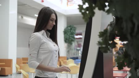 traslado : Caucasian female using automated teller machine with big digital screen while standing in shopping mall, woman verifies account balance on banking application via modern device icon