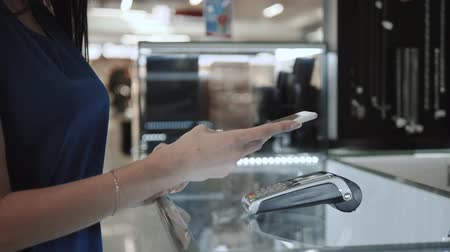 платить : Woman brunette, fashion model shopping paying with NFC technology on mobile phone, in supermarket, mall airport terminal, student in dress credit card close up Стоковые видеозаписи