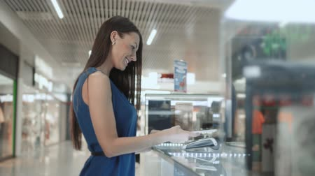 caixa : Woman brunette, fashion model shopping paying with NFC technology on mobile phone, in supermarket, mall airport terminal, student in dress credit card