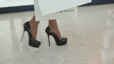 high heels : Close up shot of young woman leg carrying colorful shopping bags while walking in shopping mall on high heels black