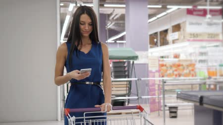troli : Woman using mobile phone while shopping in supermarket, trolley mall grocery shop store