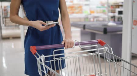 gündelik : Woman using mobile phone while shopping in supermarket, trolley mall grocery shop store