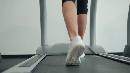 tornacipő : A close up of a woman running on a treadmill. White sneakers shoes sport. Female runner training fast athlete