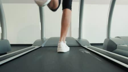 tornacipő : A close up of a woman running on a treadmill fast run. White sneakers shoes sport. Female runner training fast athlete