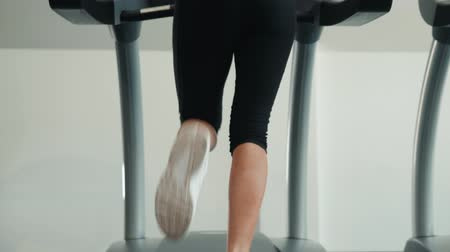 cardio workout : A close up of a woman running on a treadmill fast run. White sneakers shoes sport. Female runner training fast athlete