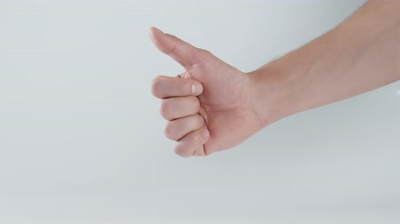 jóváhagyott : Closeup of male hand showing thumbs up sign against white background close up macro Stock mozgókép