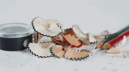 aparas de madeira : Wooden colorful pencils with sharpening shavings, on white background close up studio macro Vídeos
