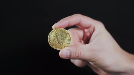 поставщик : mans hand holding golden Bitcoin on black background close up litecoin ethereum neo Стоковые видеозаписи