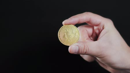 penny : mans hand holding golden Bitcoin on black background close up litecoin ethereum neo Stock Footage