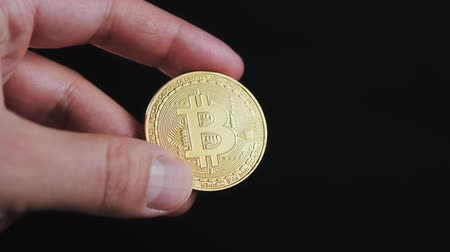 mijnwerker : mans hand holding golden Bitcoin on black background close up litecoin ethereum neo Stockvideo