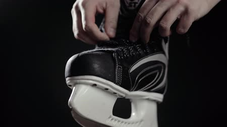koronka : A player in hockey, ties laces on skates, a black background. Close up hand man prepare for game ice canadian professional