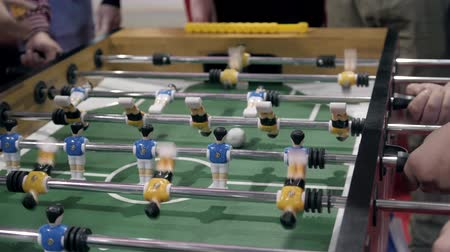 péntek : Handsome cheerful men having fun on event playing table soccer close up sport competition contest football Stock mozgókép