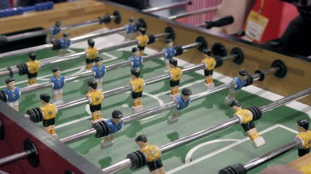 modern manhood : Handsome cheerful men having fun on event playing table soccer close up sport competition contest football Stock Footage