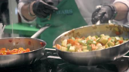 Hands of cook frying vegetables on pan colorfull color chef restaurant catering close up Stok Video