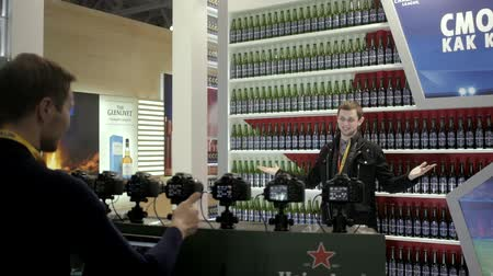 celebrity : 21 MARCH, 2018, Moscow, RUSSIA: METRO EXPO Bottles of beer put on a rack of a supermarket food expo lot of market: Model poses for photographers Stock Footage