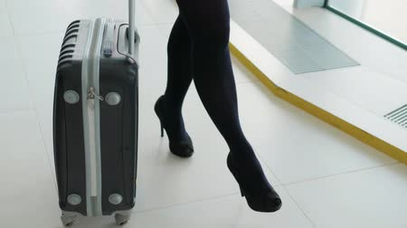 nyilvános : Close up of woman carrying suitcase at the airport terminal and hurry up for check in on holiday or business trip. Happy heels