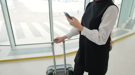 reconhecimento : Tourist woman in international airport terminal with luggage using smart phone. Voice recognition text message command helper