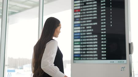 menetrend : Travel woman using smartphone at airport. Young caucasian traveler checking boarding time with mobile phone app in terminal or train station. Business woman businesswoman Tourist on vacation. Information board, departures, arrivals