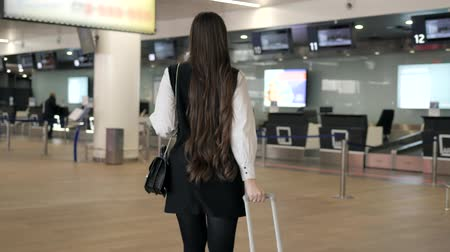 bilet : Travel woman using smartphone at airport. Young caucasian traveler checking boarding time with mobile phone app in terminal or train station. Business woman businesswoman Tourist on vacation. Information board, departures, arrivals