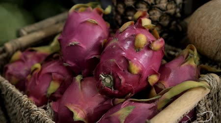 yarım uzunluk : Close up several red ripe pitaya or white pitahaya dragon fruit with one cut cross section half on market stall, high angle view market Stok Video