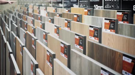 sander : A young man chooses close up hand parquet laminate flooring in the hardware store