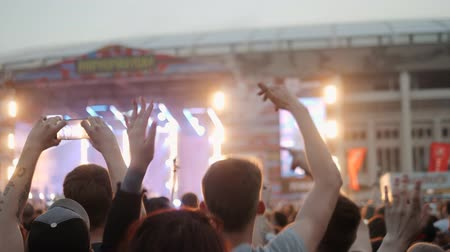 torcendo : Rear view of festival crowd raising their hands. Open air concert hip hop rap music students Stock Footage