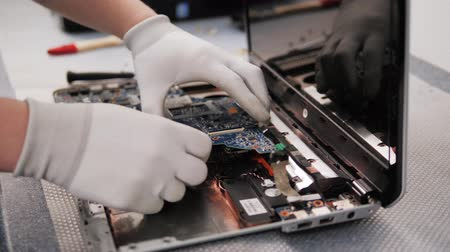 chladič : Closeup shot of male hands working on disassembling and cleaning circuit board in laptop using brush repair pc processor and change cooler