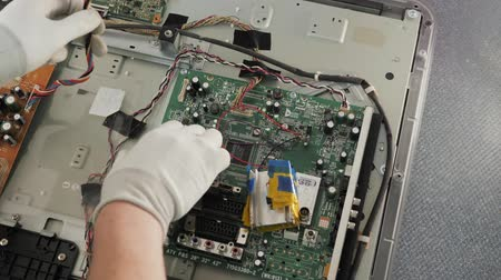 конденсатор : Technician repairing a television. Hand with voltmeter above board with components. Repair of circuits electric equipment, close up
