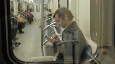 wi fi : Young handsome businessman with smartphone in subway, man student in underground railway station trasportation public cell phone communication wi fi Stock Footage