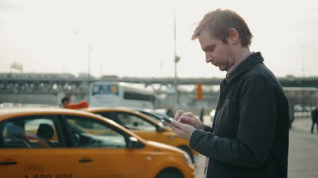 bedrijfsuitje : Elegant businessman checking taxi application app on mobile phone while walking outside airport, experienced male employer using cell telephone while waiting for trasportation orange taxi car outdoors before work travel